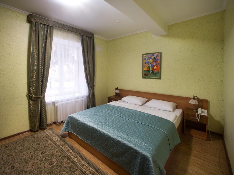 ліжко та інтер'єр кімнати у Гала Готелі Кам'янець-подільського