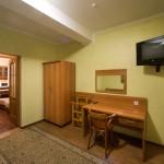 Шафа, стіл, телевізор зі супутниковим ТБ в апартаментах Гала Готелю у Кам'янець-Подільському